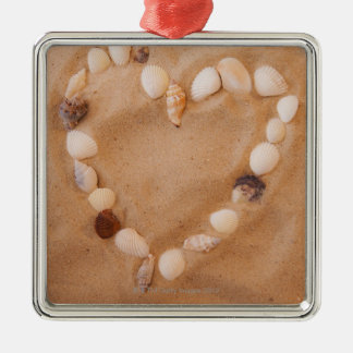 Close up of heart shape made of shells on sand christmas ornament