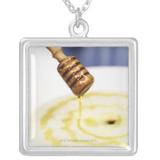 Close-up of honey dribbling on a dessert silver plated necklace