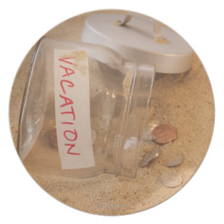 Close up of jar with coins spilled on sand dinner plate