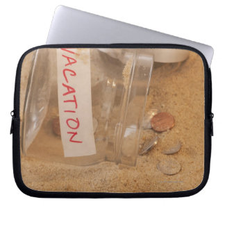 Close up of jar with coins spilled on sand laptop computer sleeve