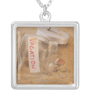Close up of jar with coins spilled on sand square pendant necklace