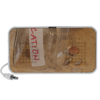 Close up of jar with coins spilled on sand speaker system
