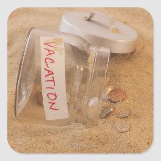 Close up of jar with coins spilled on sand square sticker