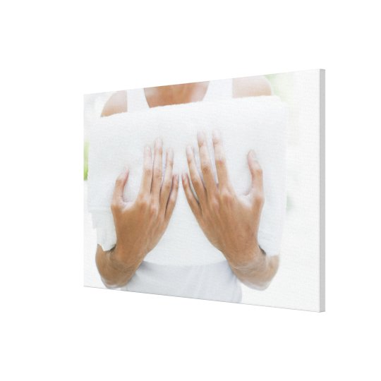 Close up of man holding towels canvas print