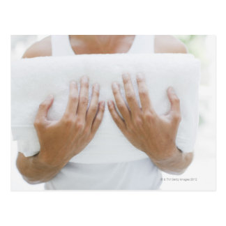 Close up of man holding towels post card