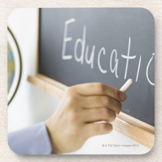 Close-up of man's hand writing ''education'' on drink coasters