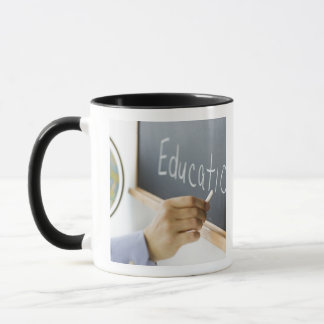 Close-up of man's hand writing ''education'' on mug