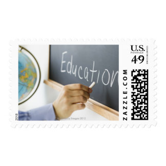 Close-up of man's hand writing ''education'' on stamps
