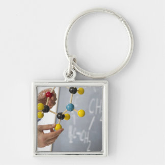 Close-up of man's hands holding molecule model, keychain