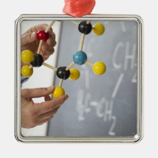 Close-up of man's hands holding molecule model, metal ornament