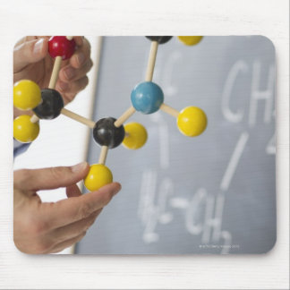 Close-up of man's hands holding molecule model, mouse pad