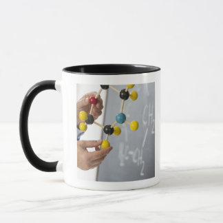 Close-up of man's hands holding molecule model, mug