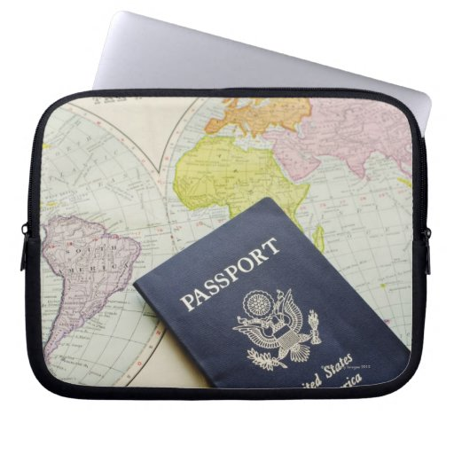 Close-up of passport lying on map computer sleeves