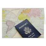 Close-up of passport lying on map greeting card