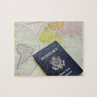 Close-up of passport lying on map jigsaw puzzle