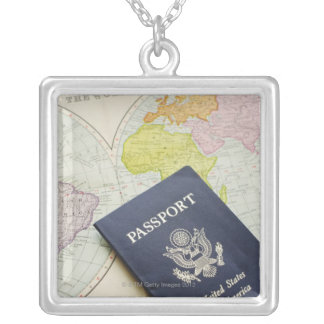 Close-up of passport lying on map necklace