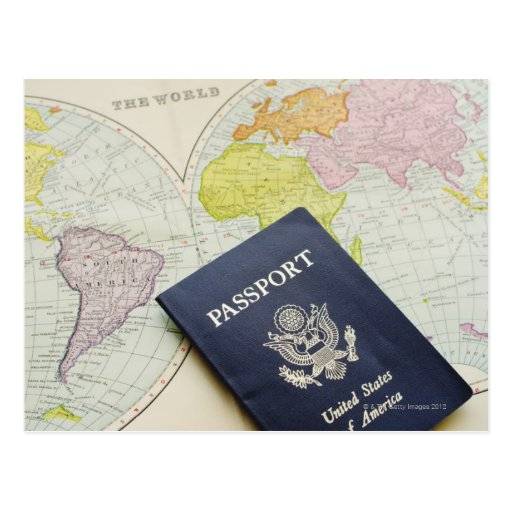 Close-up of passport lying on map post card
