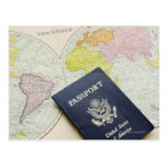 Close-up of passport lying on map postcards
