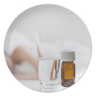 Close up of pill bottle with sick woman in party plates