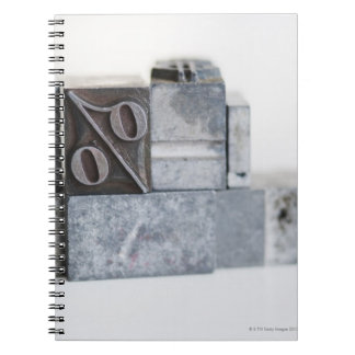 Close up of printing blocks with percentage sign spiral notebook