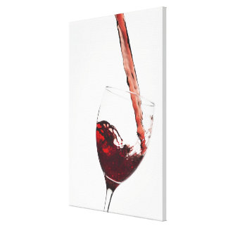 Close up of red wine being poured into glass on canvas print