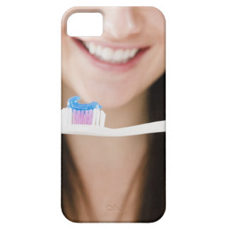 Close-up of smiling young woman holding iPhone 5 cases