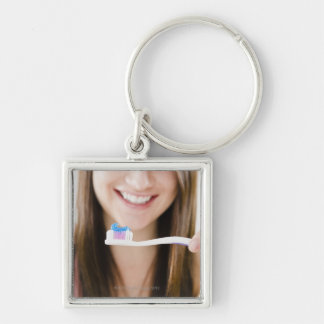 Close-up of smiling young woman holding Silver-Colored square keychain
