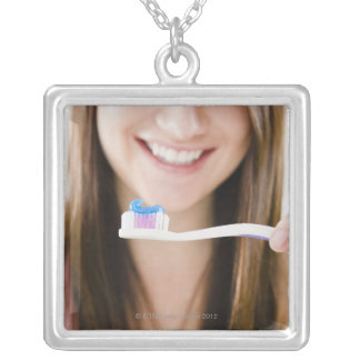 Close-up of smiling young woman holding silver plated necklace