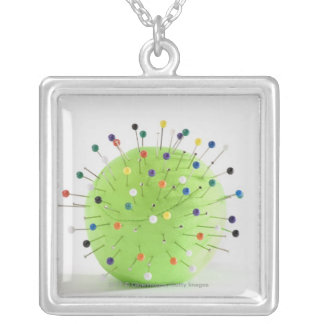 Close-up of straight pins inserted into a ball square pendant necklace