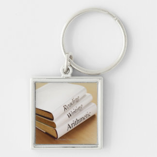 close-up of three books on a wooden surface keychain