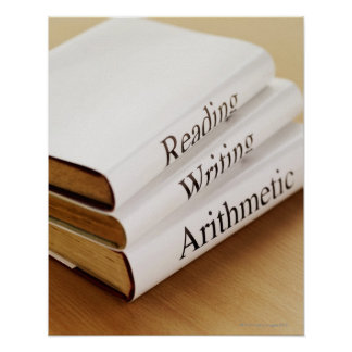 close-up of three books on a wooden surface poster