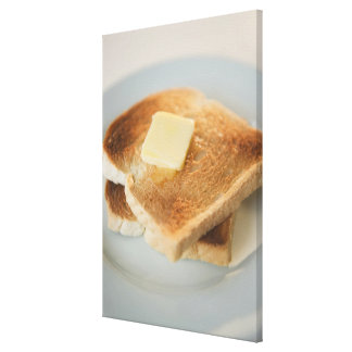 Close up of toasts with butter on plate stretched canvas prints