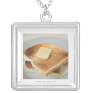 Close up of toasts with butter on plate silver plated necklace