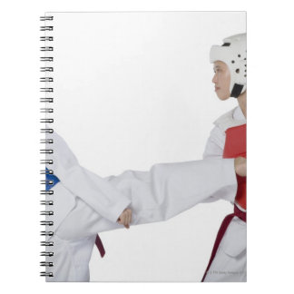 Close-up of two young women practicing spiral notebooks