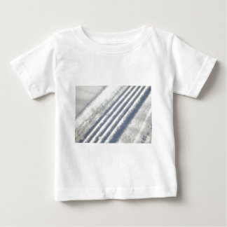 Close-up on a tyre traces in the snow baby T-Shirt