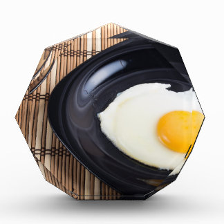 Close-up top view on a black plate with fried egg award