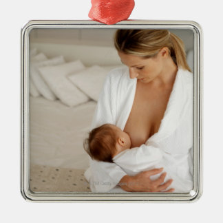 Close up view of a mother breastfeeding her baby metal ornament
