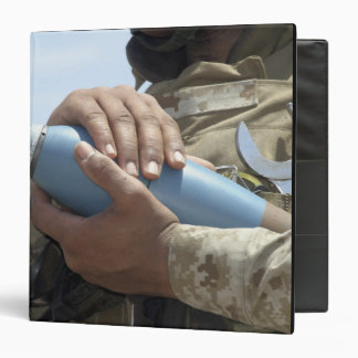 Close-up view of a soldier cradling a munition 3 ring binder