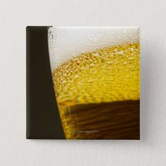 Close up view of beer, bubbles and foam in a button