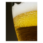 Close up view of beer, bubbles and foam in a poster