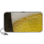 Close up view of beer, bubbles and foam in a laptop speaker
