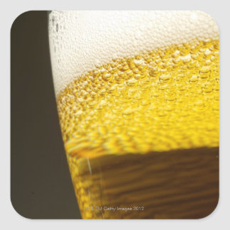 Close up view of beer, bubbles and foam in a square sticker