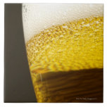 Close up view of beer, bubbles and foam in a large square tile
