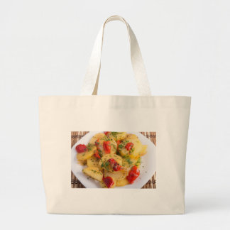 Close up view on a vegetarian dish of potatoes large tote bag