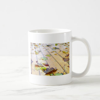 Close up view on a wet green and yellow leaves of coffee mug