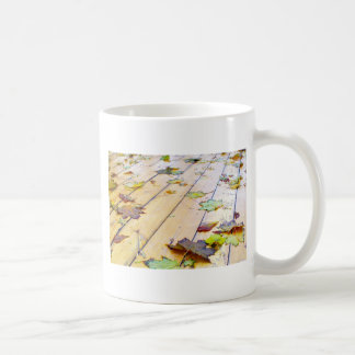 Close-up view on a wet green and yellow leaves of coffee mug