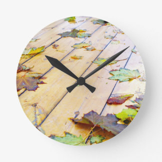 Close-up view on a wet green and yellow leaves of round wall clocks
