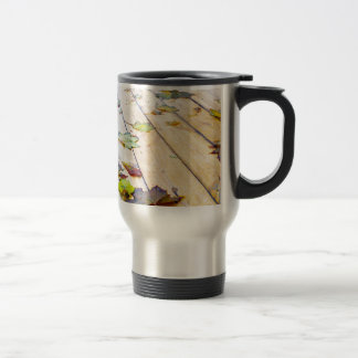 Close up view on a wet green and yellow leaves of travel mug