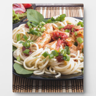 Closeup black plate with spaghetti plaque