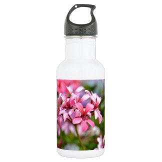 Closeup geranium flowers water bottle